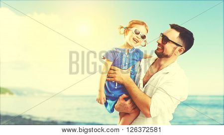 happy family father and child daughter playing and having fun in the summer by the sea on the beach