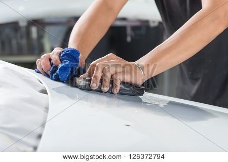 Auto body repair series : Closeup of hand sanding car hood