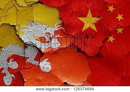 flags of Bhutan and China painted on cracked wall