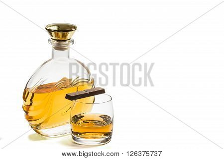 Bottle and a glass of whiskey with chocolate on a white background
