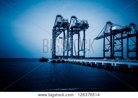 mechanical cranes lifting freight at pier,blue toned image.