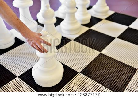 Hand moving a pawn on a giant chess game