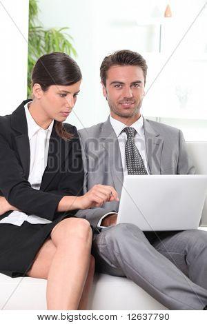 Empresario y empresaria frente a una computadora portátil