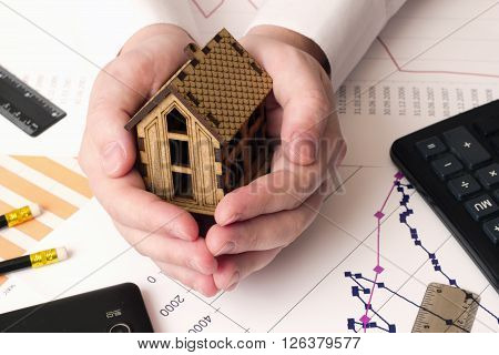 small house in the hands , calculator , graphics