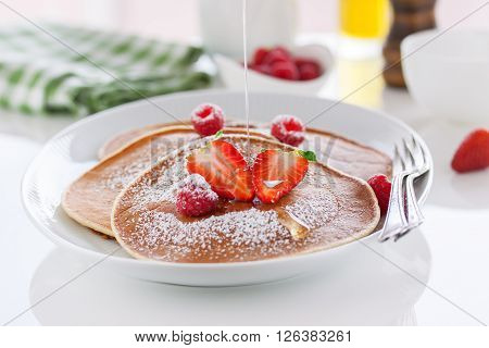 Homemade buttermilk american pancakes with fresh strawberry raspberry and honey on a white plate on a white table for breakfast closeup selective focus