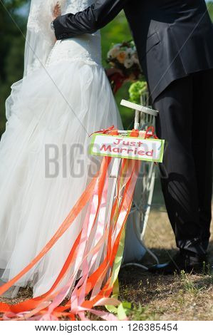 Groom and bride on white bicycle with just married sign and colorful ribbons. Outdoors. Loving couple embracing in the background.