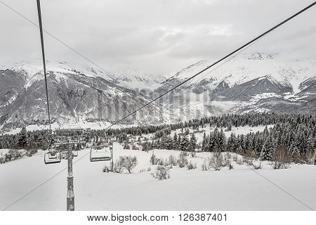 Cableway of Hatsvali Ski Station with view on the mountains and forest in snow. Georgia