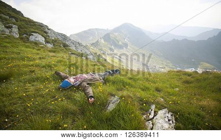 Woman hikerl lies on top of the mountain in green grass