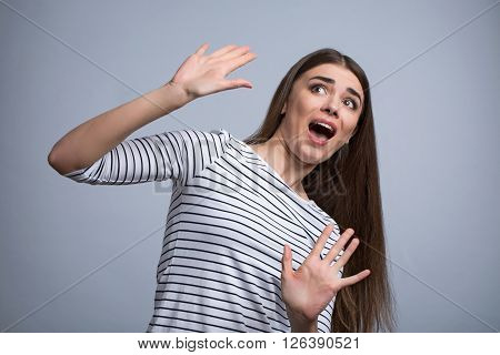 Pleasant scared  beautiful girl holding her hands up   evading danger while standing isolated on grey background