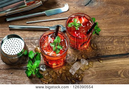 Red drink with strawberry mint leaves ice. Shaker and cocktail bar tools