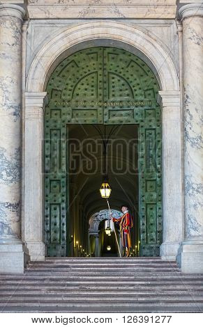 Vatican Italy - June 26 2014: Vatican guard stands in front of Vatican Museum in Rome Italy. The Swiss Guards are responsible for the security of Vatican.