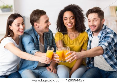 Cheers.  Positive delighted smiling sitting on the couch and drinking juice   while spending leisure time together