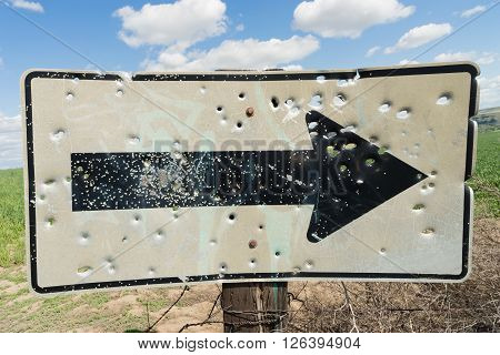 Someone or several people have damaged a road sign by shooting it