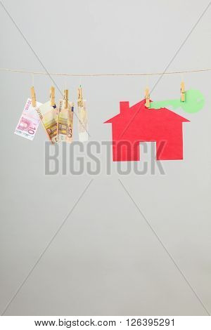 Red house with green key and banknotes cash hang on laundry line on grey background. Selling and buying home concept.