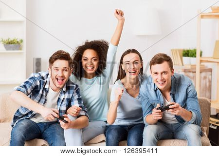 Spirit of competition. Cheerful delighted pleasant smiling friends playing video games and expressing gladness while sitting on the couch