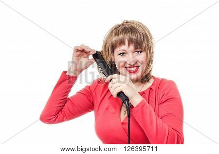 The woman in a red dress straightens hair the curling iron
