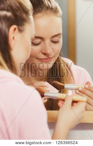 Woman Applying Bronzing Powder With Brush To Her Skin