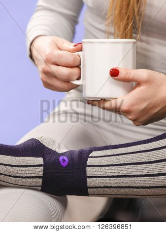 Woman in winter gray sports thermal underwear for skiing training holds mug with tea or coffee warming herself studio shot on violet