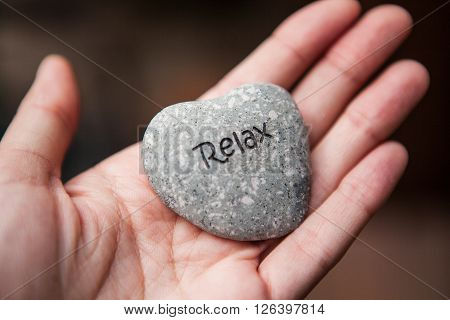 Hands holding pebble stones with the word relax