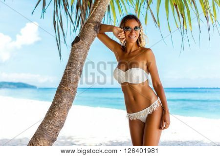 Young woman wearing white bikini posing under palm tree over sea view at tropical beach