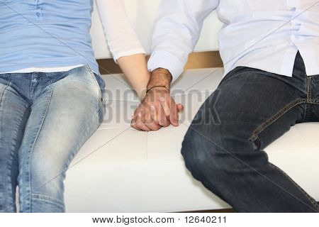 Couple sitting on a sofa holding hands