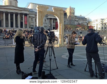 LONDON UK - APRIL 19 2016: News journalists report on the Arch of Triumph from the historic city of Palmyra in Syria recreated in 3D printed marble and erected in Trafalgar Square London. A project by the Institute of Digital Archaeology the arch will tra