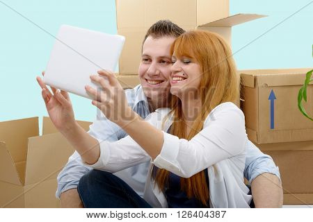 a happy couple sitting on the floor taking selfie in their new house