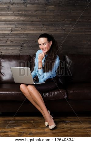 Business lady looking to the camera on the brown wooden background for use e.g. in collages, presentation