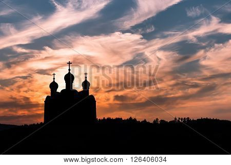 Silhouette of Christian church against colorful sunset sky