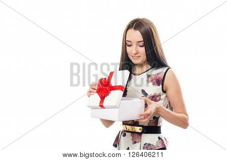 The beautiful woman in a dress opens a gift