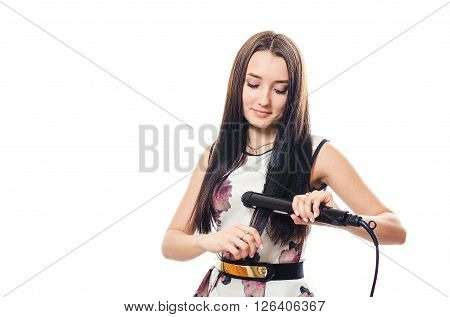 The young woman in a dress irons hair the iron