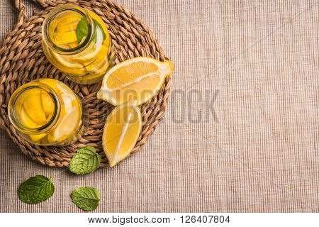 Slices and half fresh juicy lemon with mint leaves. Top view with copy space.