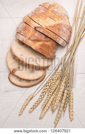 Fresh homemade bread and wheat spike on wooden background. Top view with copy space.