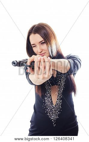 The serious young woman in a dress aims from the pistol
