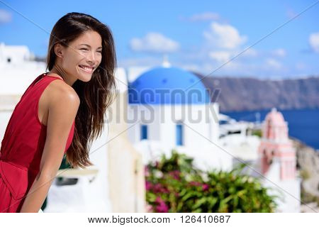 Santorini tourist Thira Greece island tourism - Asian woman wearing red dress on summer travel looking at view with the famous attraction three domes chapel church. Luxury destination.