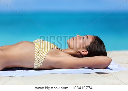 Summer beach vacation woman relaxing sunbathing and suntanning. Sexy young ethnic adult in yellow stripes bikini sleeping lying down on white sand dreaming on tropical travel tourist destination.