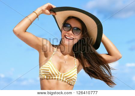 Summer beach vacation woman enjoying the sun in bikini and sunglasses having fun happy with hair in wind holding on hat. Sexy Asian young adult on towel for tropical travel holidays concept.