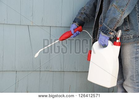 man spray pesticide on the house exterior