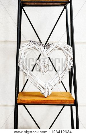 Heart within a heart decorative prop standing on metal and wooden stand against the white wall
