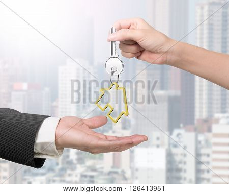 Woman Hand Giving Key With House Keyring To Man Hand