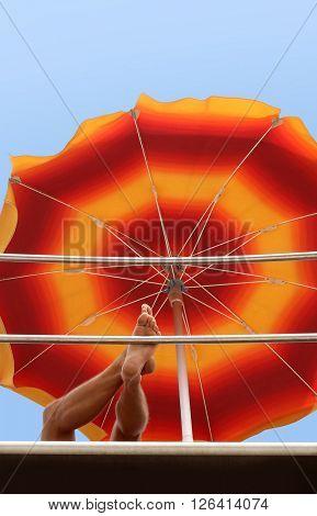 Man is resting under beach umbrella