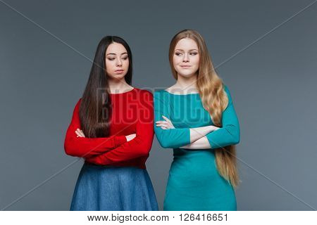 Two offended girlfriend standing with arms folded and looking at each other over gray background