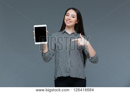 Smiling businesswoman pointing finger on blank tablet computer screen over gray background