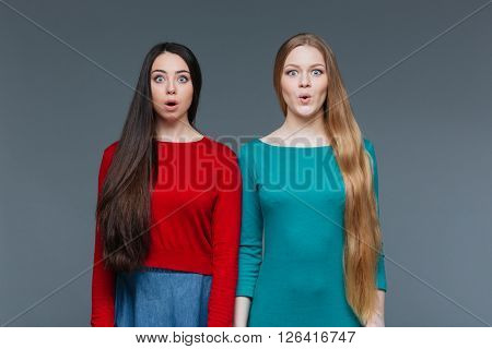 Two amazed girl standing over gray background and looking at camera
