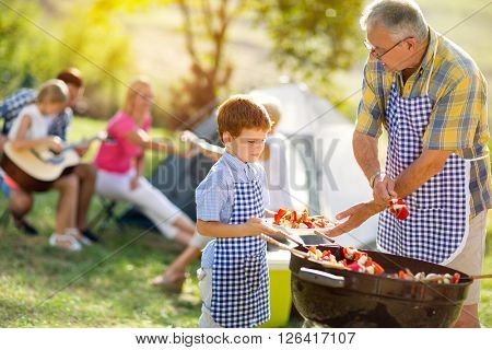 grandfather giving grandson grillied meat for dinner