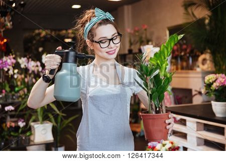 Happy beautiful young woman florist in apron watering plants with pulvelizer in flower shop
