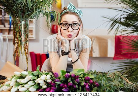Portrait of charming amusing young woman florist making funny face standing in flower shop