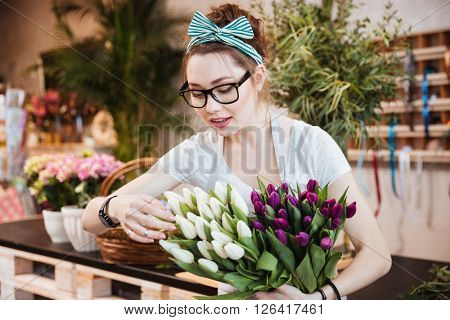 Cute lovely young woman florist in glasses taking care of tulips in flower shop