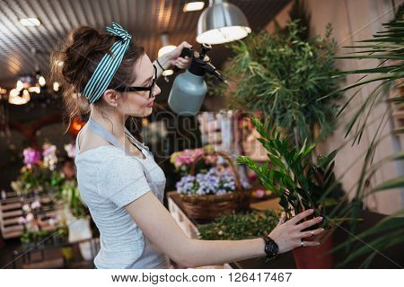 Smiling cute young woman florist standing and watering plants with water sprayer in flower shop