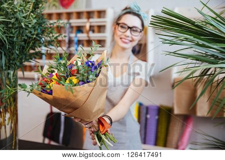 Happy charming young woman florist giving bouquet of colorful flowers to you